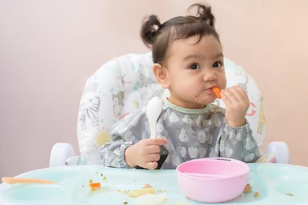Een schattig aziatisch meisje dat op de eettafel zit, oefent zelf met het eten van wortel en ander voedsel, baby-led weaning-concept