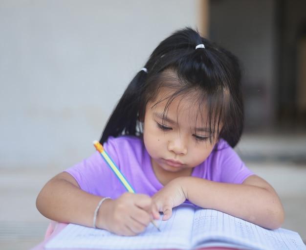 Een schattig aziatisch meisje doet overdag huiswerk in haar huis.
