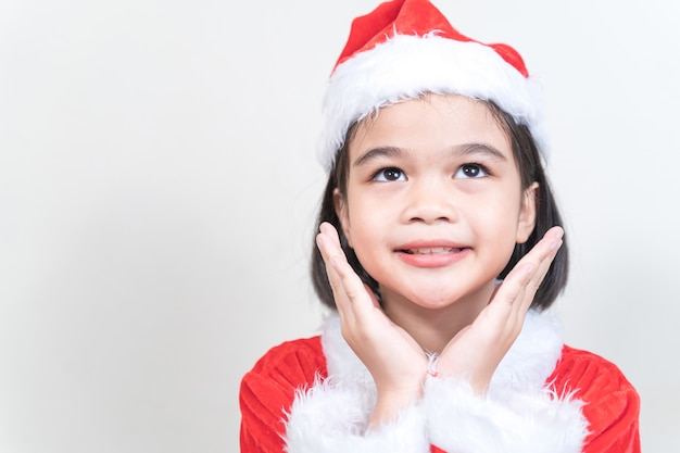 Een schattig aziatisch meisje in een rode kerstmanjurk die de kerstboom versiert op kerstavond