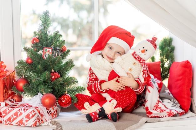 Een schattig babymeisje met een sneeuwpop in haar handen zit op de vensterbank bij het raam van het huis bij de kerstboom en wacht op het nieuwe jaar of kerstmis in een kerstmanhoed en glimlacht