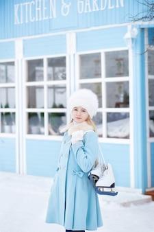 Een schattig blond meisje gaat buiten schaatsen. een meisje in een blauwe jas en bontmuts met schaatsen in het winterhuis. weekendactiviteiten bij koud weer. kerstmis, wintervakantie concept. wintersport.