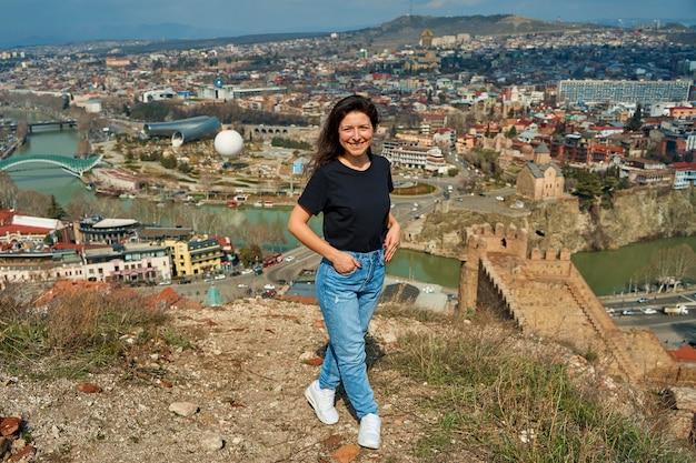 Een schattig brunette meisje geniet vanaf de heuvel van het prachtige landschap van tbilisi. de hele stad aan haar voeten.