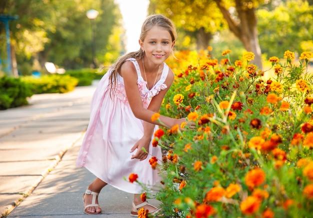 Een schattig charmant meisje in een mooie roze jurk ruikt vurige goudsbloemen in een helder park op een zonnige dag op een langverwachte vakantie