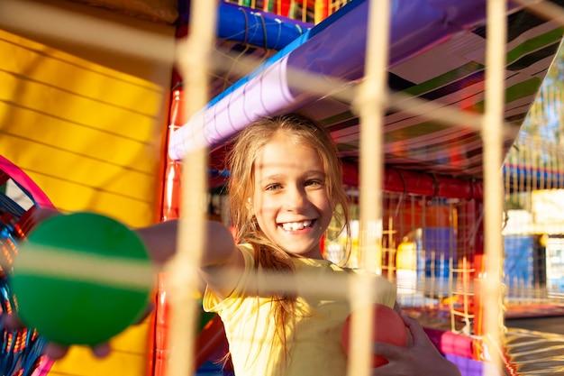 Een schattig grappig meisje zit in een speeltuin met zachte en heldere apparatuur en gooit kleurrijke ballen