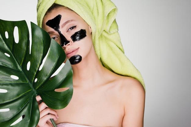 Een schattig jong meisje met een groene handdoek op haar hoofd bracht een zwart masker aan op de probleemzones op haar gezicht