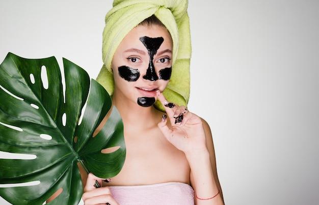 Een schattig jong meisje met een groene handdoek op haar hoofd paste een zwart masker toe op de probleemgebieden op haar gezicht, de dag van de spa