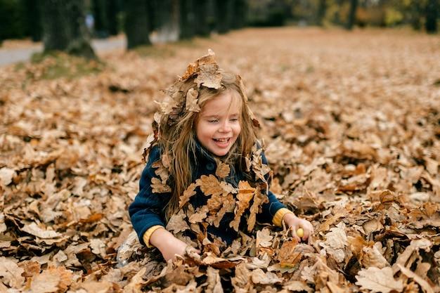 Een schattig jong meisje speelt in bladeren