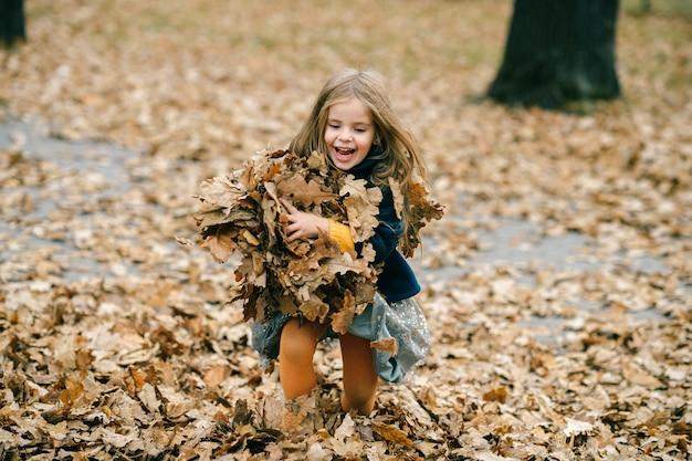 Een schattig jong meisje speelt met bladeren