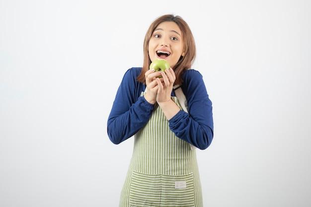 Een schattig jong meisjesmodel in schort dat een groene verse appel houdt.