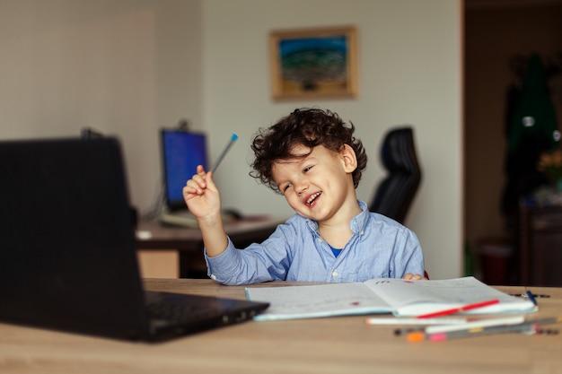 Een schattig jongetje met krullen zit op zijn laptop aan de tafel in de voorschoolse leeftijd