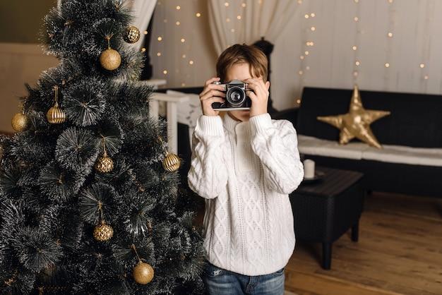 Een schattig kind fotografeert op een retro camera tegen de achtergrond van een kunstmatige kerstboom met gouden ballen.