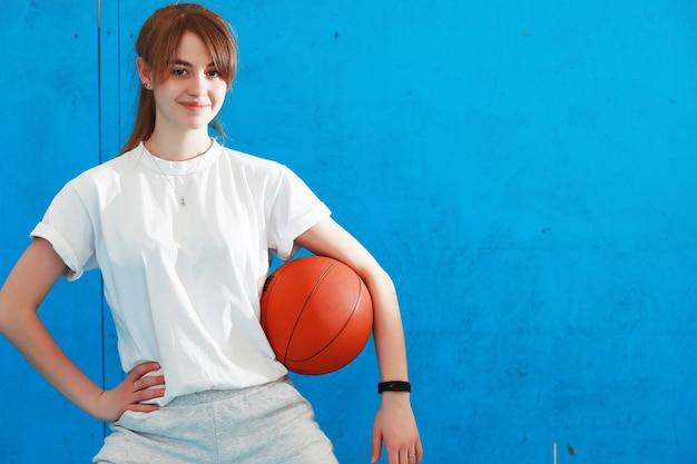 Een schattig kind, meisje houdt zich bezig met sport, ze kijkt opzij tijdens het sporten met basketbal. geïsoleerde onblue achtergrond. fitness, training, actief levensstijlconcept. horizontaal schot. vooraanzicht