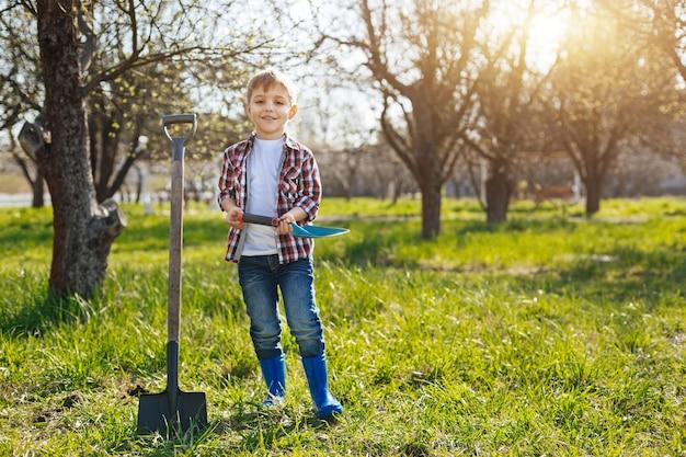 Een schattig kind staat met een aarde schep in een huis tuin en kijkt naar de voorkant op een mooie zonnige dag