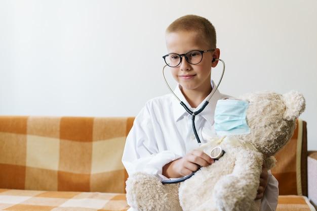 Een schattig kind verkleed als dokter speelt met een teddybeer terwijl het zijn ademhaling controleert met een s...