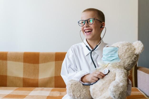 Een schattig kind verkleed als dokter speelt met teddybeer die zijn ademhaling controleert met een stethoscoop...