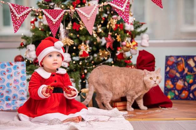Een schattig kind verkleed als kerstman speelt in de buurt van een versierde kerstboom in de woonkamer. een kat loopt rond de geschenken.