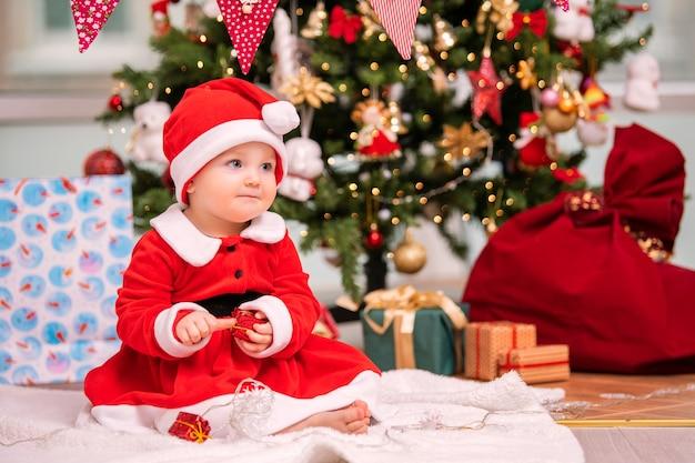Een schattig kind verkleed als kerstman speelt in de buurt van een versierde kerstboom in de woonkamer.