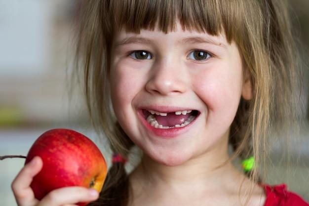 Een schattig klein krullend tandenloos meisje glimlacht en houdt een rode appel vast. portret van een gelukkige baby die een rode appel eet. het kind verliest melktanden. gezonde voeding