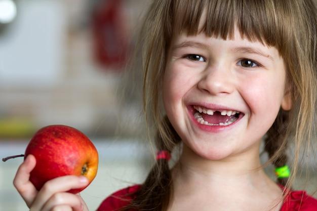 Een schattig klein krullend tandenloos meisje glimlacht en houdt een rode appel vast.