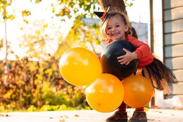 Een schattig klein meisje 2-3 in een oranje en zwart heksenkostuum met ballonnen staat op het terras van een houten huis