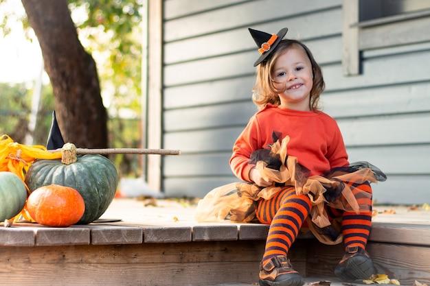 Een schattig klein meisje 2-3 in een oranje en zwart heksenkostuum zit naast pompoenen op het terras van een houten grijs huis