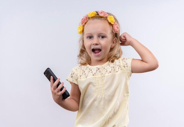 Een schattig klein meisje draagt een geel shirt in een bloemenhoofdband die hand op het hoofd met open mond houdt terwijl ze een mobiele telefoon vasthoudt op een witte muur