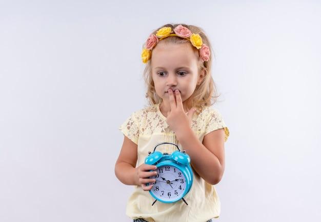 Een schattig klein meisje draagt een geel shirt in een bloemenhoofdband en denkt met de vinger op de mond terwijl ze een blauwe wekker op een witte muur houdt