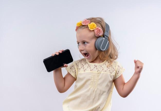 Een schattig klein meisje draagt een geel shirt in een bloemenhoofdband, luisteren en zingen vanaf de mobiele telefoon met koptelefoon op een witte muur