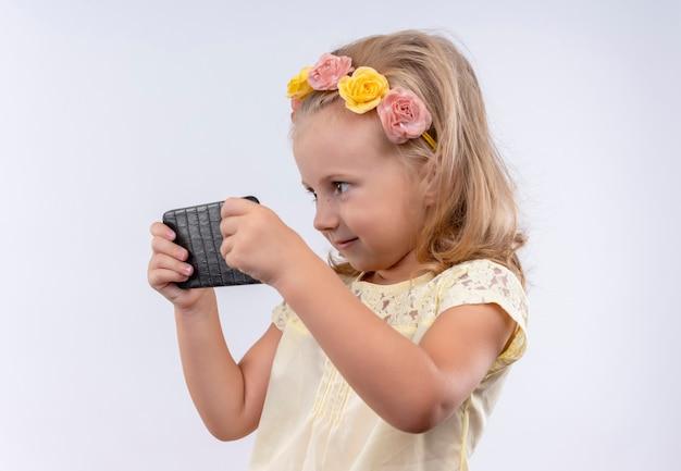 Een schattig klein meisje draagt een geel shirt in een bloemenhoofdband speelspel op een mobiele telefoon op een witte muur