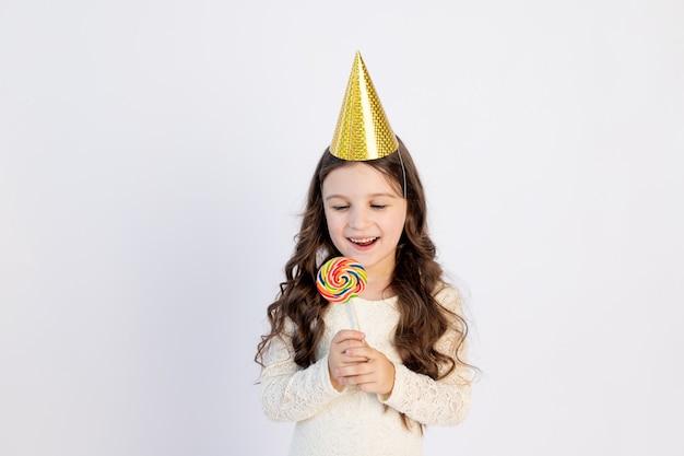 Een schattig klein meisje eet een grote lolly in een feestelijke hoed op een witte geïsoleerde achtergrond. ruimte voor tekst. klein meisje viert verjaardag, concept vakantie