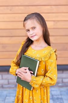 Een schattig klein meisje houdt een boek vast op een zomerdag in een stadspark, glimlacht en kijkt naar de camera. opleiding.