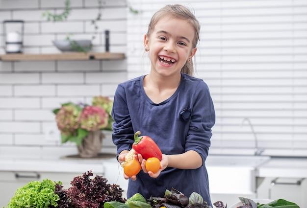 Een schattig klein meisje houdt verse groente vast tijdens het voorbereiden van een salade kopie ruimte.
