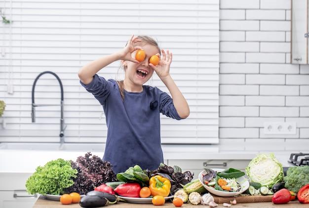 Een schattig klein meisje houdt verse groenten vast tijdens het voorbereiden van een salade kopie ruimte.
