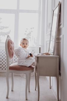 Een schattig klein meisje in een badjas houdt een make-up kwast, doet make-up en kijkt in de camera. babymeisje zit op de stoel bij de klassieke spiegel. kindermode. klein meisje fashionista