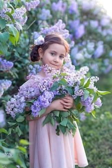 Een schattig klein meisje in een jurk houdt een mand met bloeiende seringen vast. zomer wandelingen. bloeiende bladeren.