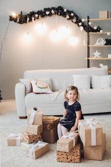Een schattig klein meisje in een jurk zit omringd door vele dozen met kerstcadeaus en wil ze openen