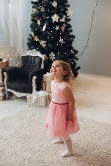 Een schattig klein meisje in een mooie jurk heeft veel plezier in de buurt van de kerstboom thuis