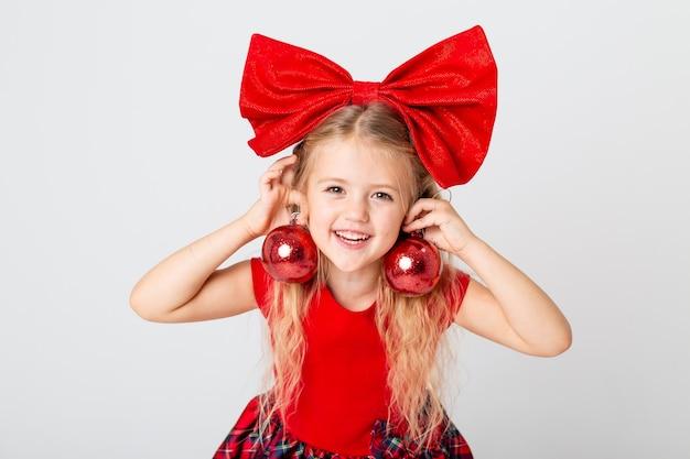 Een schattig klein meisje in een rode jurk en strik op haar hoofd met kerstboom speelgoed. witte achtergrond, ruimte voor tekst