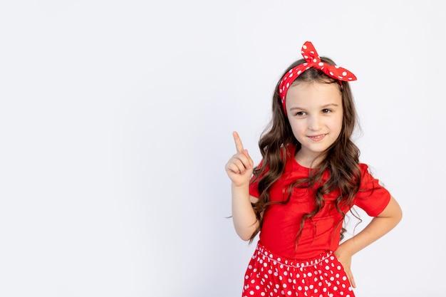 Een schattig klein meisje in een rode outfit op een witte achtergrond geïsoleerd toont een duim omhoog. ruimte voor tekst. het concept van de viering en verkoop