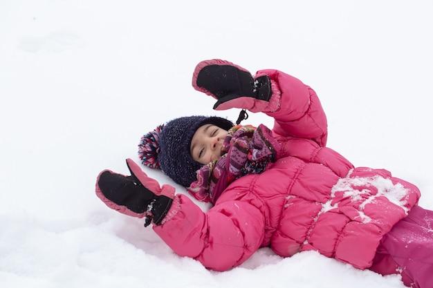 Een schattig klein meisje in een roze jasje en een hoed speelt in de sneeuw. winter kinderentertainment concept.