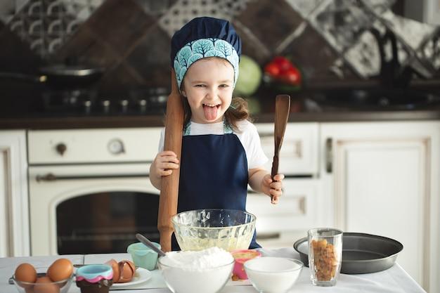 Een schattig klein meisje in een schort en een koksmuts houdt een deegroller en een houten spatel vast en laat haar tong zien.