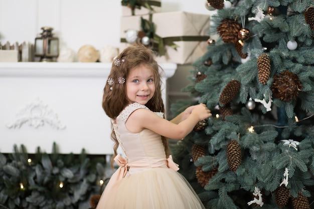 Een schattig klein meisje in een weelderige beige jurk hangt kegels aan de kerstboom die in het huis staat. kerstverhaal, gelukkige jeugd.