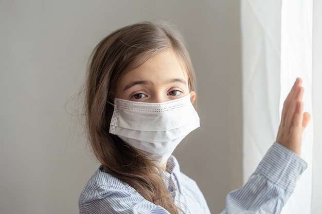 Een schattig klein meisje in een wegwerp beschermend masker tegen het coronavirus. jeugdconcept tijdens pandemie en quarantaine.