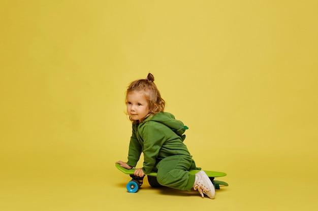 Een schattig klein meisje in stijlvolle groene outfit zit op het skateboard op de gele achtergrond, geïsoleerd met kopie ruimte. kindermode