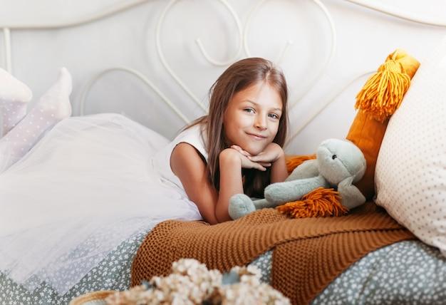 Een schattig klein meisje ligt op het bed in een witte jurk. een blik op de camera
