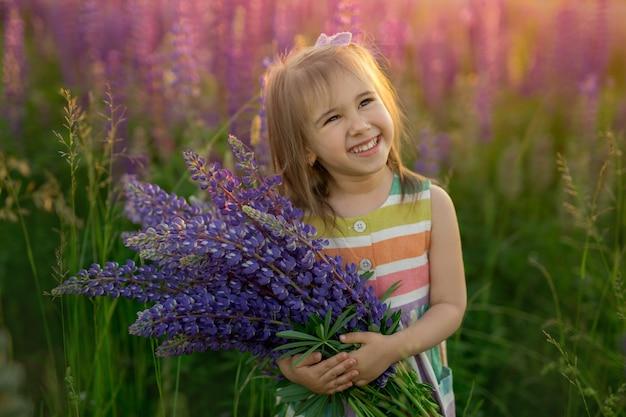 Een schattig klein meisje met een boeket lupines in een veld met paarse bloemen lacht lief en kijkt omhoog