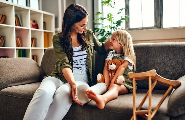 Een schattig klein meisje met een gebroken been in het gips zit met haar moeder op de bank en knuffelt een teddybeer thuis. er zijn krukken bij de bank voor een snelle revalidatie.