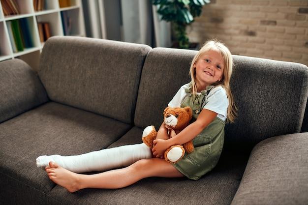 Een schattig klein meisje met een gebroken been in het gips zit thuis een teddybeer te knuffelen op de bank.