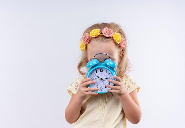 Een schattig klein meisje met een geel shirt in een bloemenhoofdband die de tijd laat zien terwijl ze een blauwe wekker op een witte muur houdt