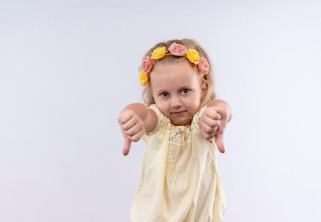 Een schattig klein meisje met een geel shirt in een bloemenhoofdband met duimen op een witte muur